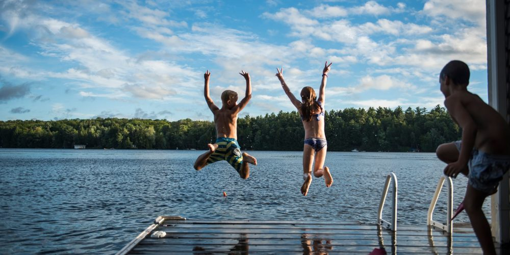 Kids,Jumping,Into,The,Lake,With,Their,Arms,Thrown,Up