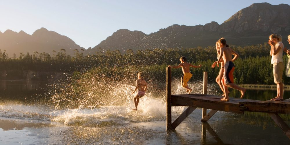 Horizontal,Shot,Of,A,Multi-generational,Family,Jumping,From,Jetty,Into