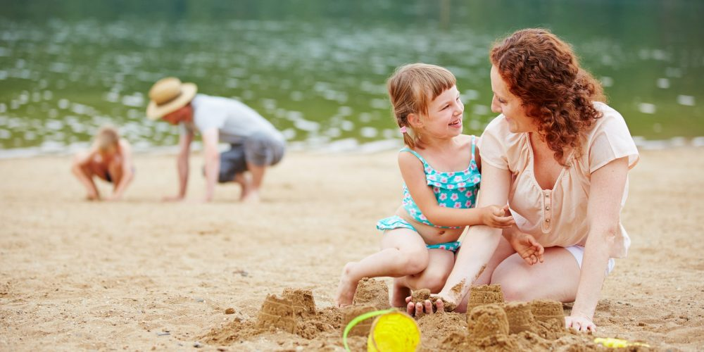 Mother,And,Daughter,Building,A,Sand,Castle,Together,On,A