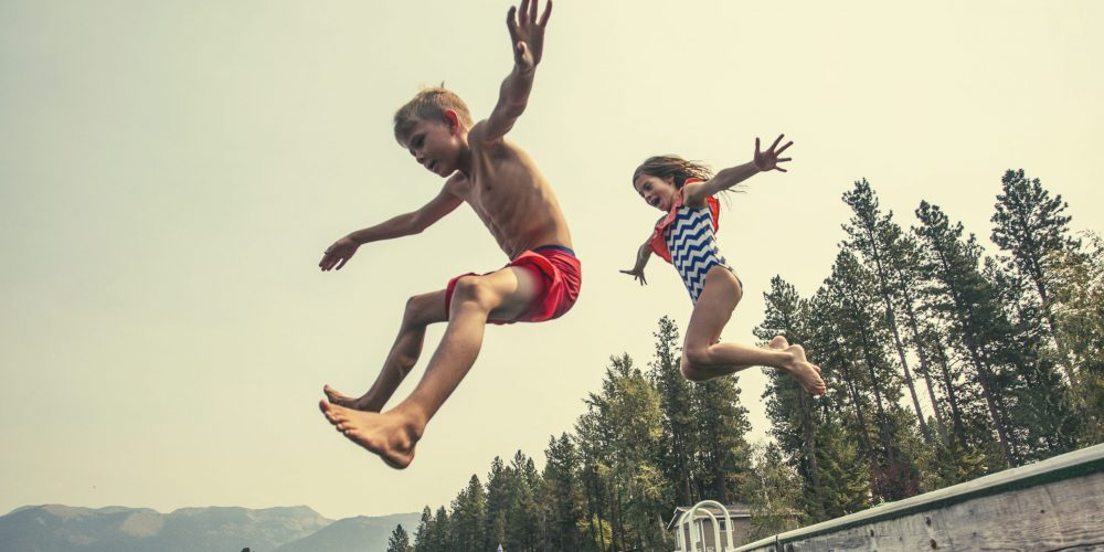 Kids,Jumping,Off,The,Dock,Into,A,Beautiful,Mountain,Lake.