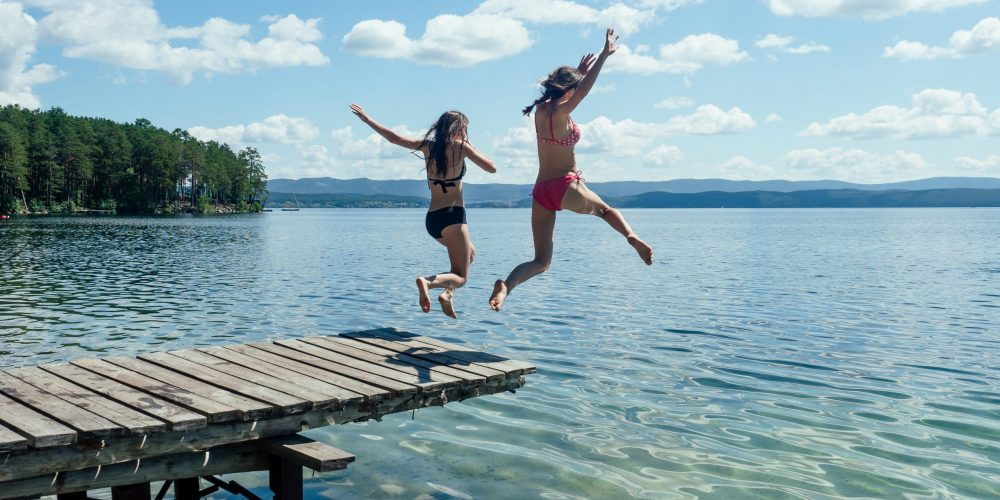 Two,Girls,In,Bathing,Suits,Jumping,From,A,Wooden,Pier